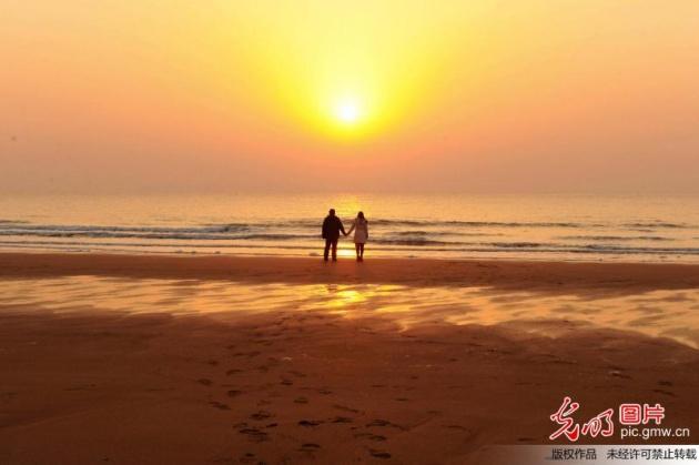 2016年2月8日,山东省青岛市金沙滩,猴年第一轮旭日从海面缓缓升起。 当日,农历大年初一。市民们来到海边观看猴年第一轮日出。冬泳爱好者迎着猴年的朝阳来到海边游泳,市民在海边漫步健身。猴年新春,一派祥和。