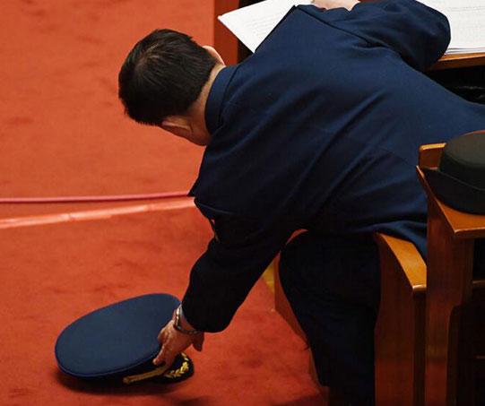一名代表在捡起不小心掉在地上的帽子