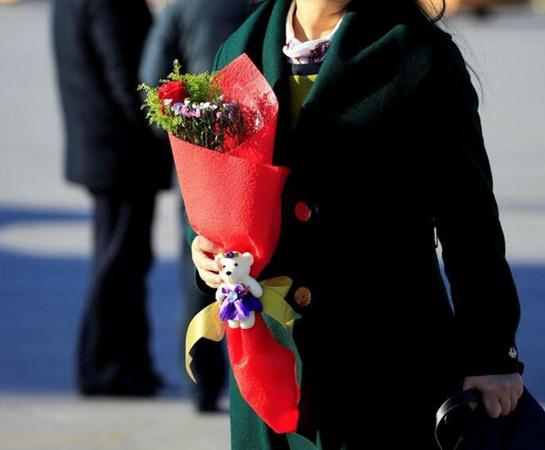 一名代表在人民大会堂外捧着一束鲜花